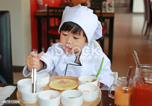 istock Kid girl in a suit of the little chef make mini pizza. 667810368