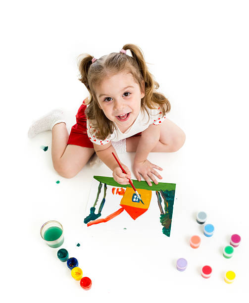 Kid girl is painting. Top view. stock photo