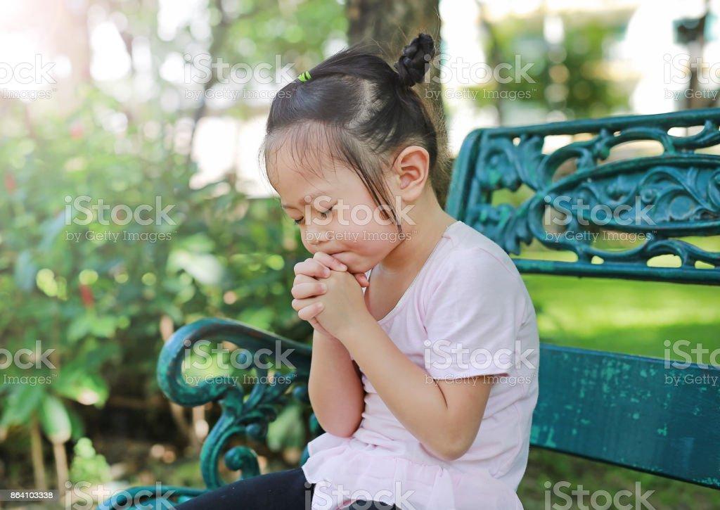 Kid girl praying in the garden. royalty-free stock photo