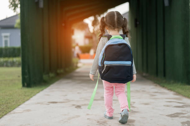 Kid girl pupil walking back to home after learning study school alone with schoolbag,preschool and kindergarten education concept. stock photo