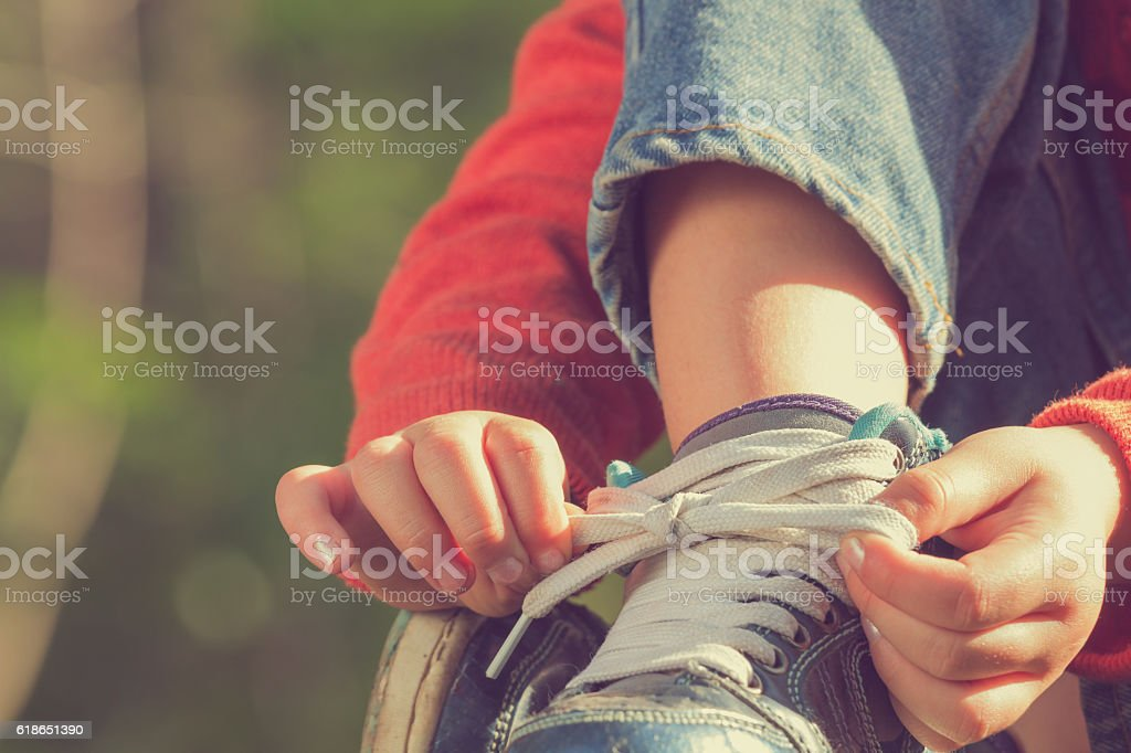 Kid girl tying her shoes. stock photo