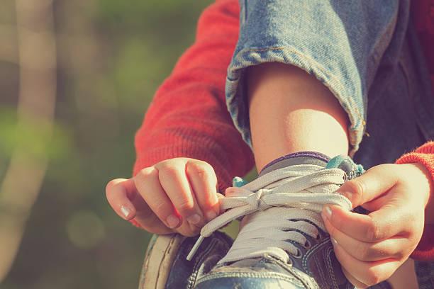 kid girl tying her shoes. - schnürsenkel stock-fotos und bilder