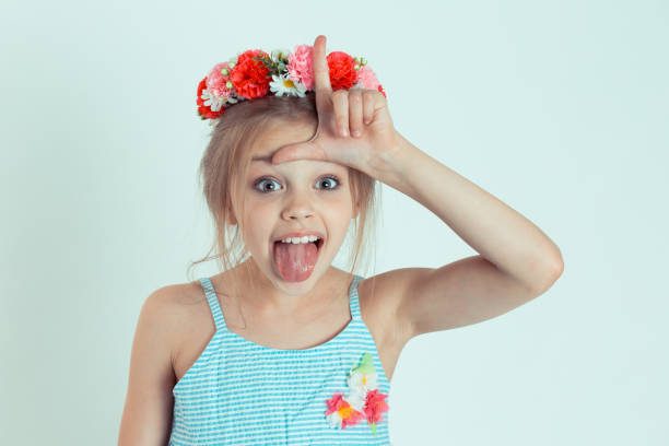 kid giving loser sign on forehead with tongue out isolated on light green wall background Closeup portrait young unhappy girl, kid giving loser sign on forehead looking at tongue out isolated on light green wall background. Negative human emotion facial expression body language reaction antagonize stock pictures, royalty-free photos & images