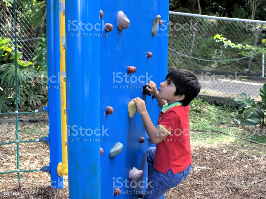 Kid going up on climbing wall at park - Стоковые фото Австралия - Австралазия роялти-фри