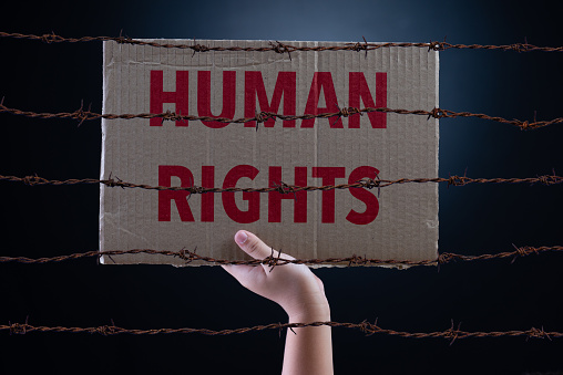 Kid hand holding cardboard paper with HUMAN RIGHTS text and rusty sharp bare wire on dark background, conceptual image.