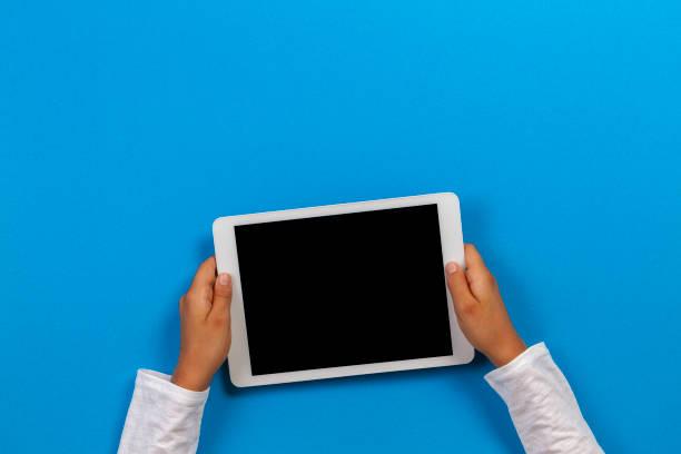 Kind Hand hält weißen Tablet-Computer auf hellblauem Hintergrund – Foto