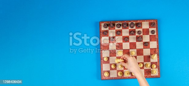 Kid hands over a chessboard playing chess game on blue background