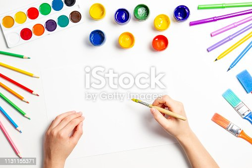 Kid hands painting at the table with art supplies, top view