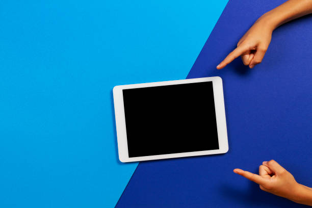 Kinderhände zeigen Finger auf leeren Tablet-Computer auf blauem Hintergrund – Foto