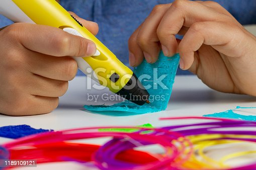 1082038948 istock photo Kid hands with 3d pen creating new item 1189109121