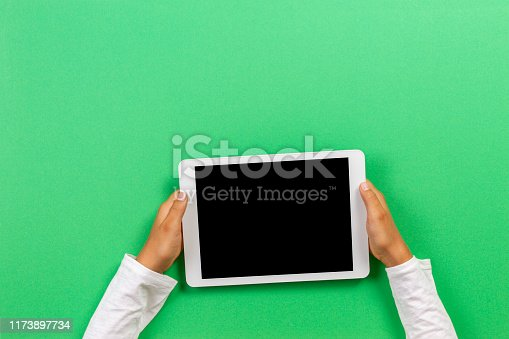 Kid hands with tablet computer on light green background