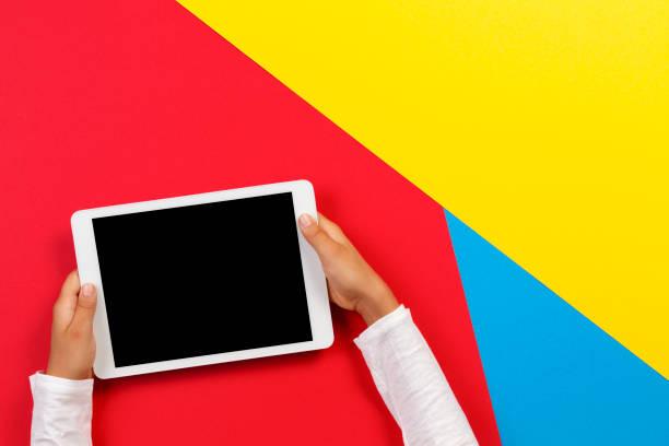 Kinderhände mit Tablet-Computer auf rotem, gelbem und blauem Hintergrund – Foto