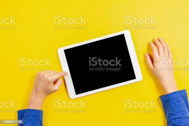 Kid hands with tablet computer on yellow background picture id1089821106?b=1&k=6&m=1089821106&s=612x612&h=lxlfgxggetfninc0bmsebmvarfqgn7xnnqapzp4hbge=