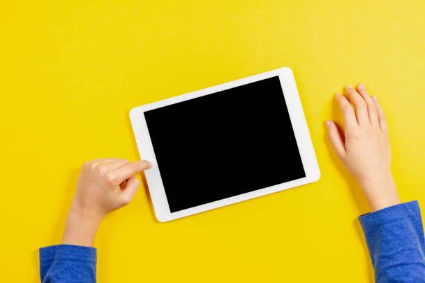 kind-hände mit tablet-pc auf gelbem hintergrund - tablet stock-fotos und bilder