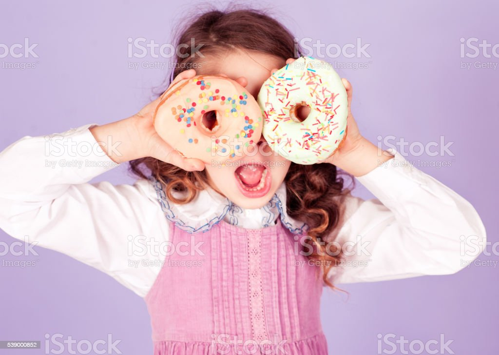 Kid having fun with donuts stock photo