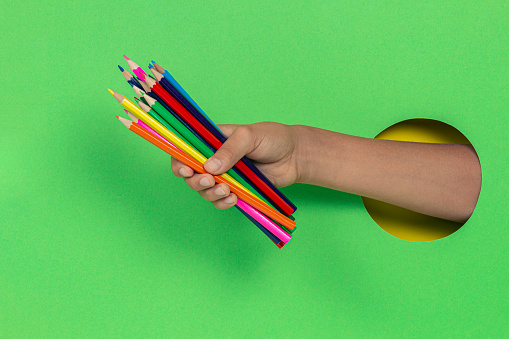 Kid holding colored pencils in hand through hole on light green background.