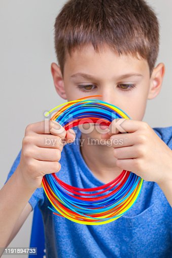899701486 istock photo Kid holding colorful filaments for 3d pen and choose color for new item 1191894733