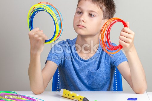 1082038948 istock photo Kid holding colorful filaments for 3d pen and choose color for new item 1191894814