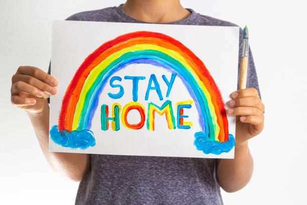 Kind halten Zeichnung Bild mit Regenbogen mit Worten Bleiben Sie zu Hause. Social-Media-Kampagne zur Coronavirus-Prävention – Foto