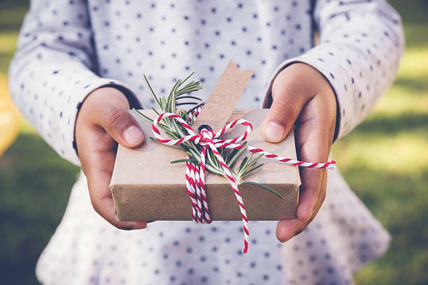 kid holding eco gift box with brown tag, holidays background - eco bastelarbeiten stock-fotos und bilder