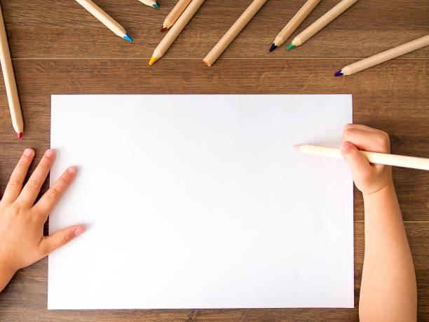 kind mit bleistift über leere blatt papier - zeichnen lernen mit bleistift stock-fotos und bilder