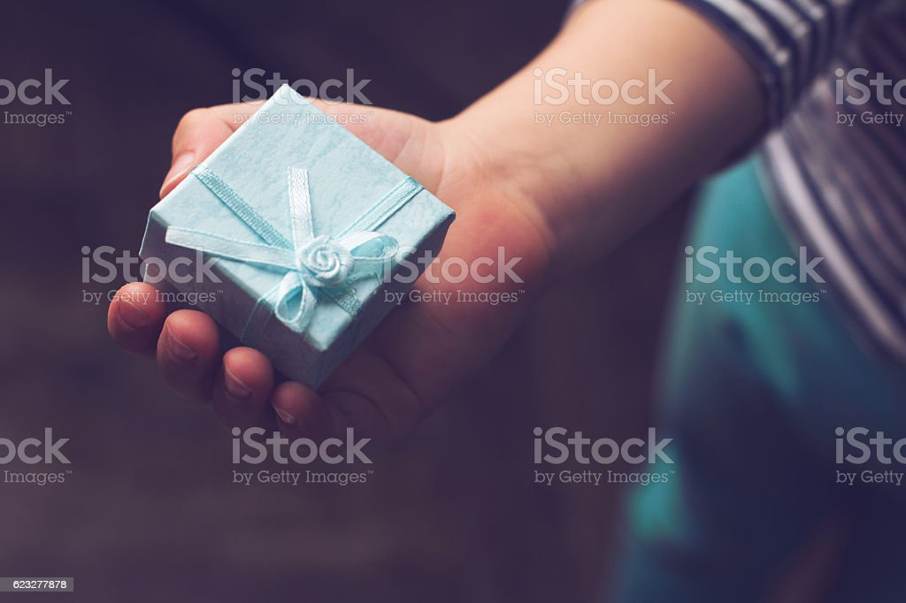 kid holding small blue gift box with ribbon in hand stock photo