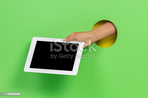 655532196 istock photo Kid holding tablet computer in hand through hole on light green background 1173896888