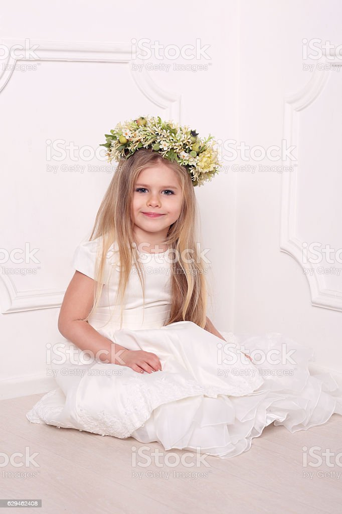 Kid in dress with flower head wreath. White background stock photo