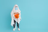 istock kid in ghost costume wearing face mask 1279828557