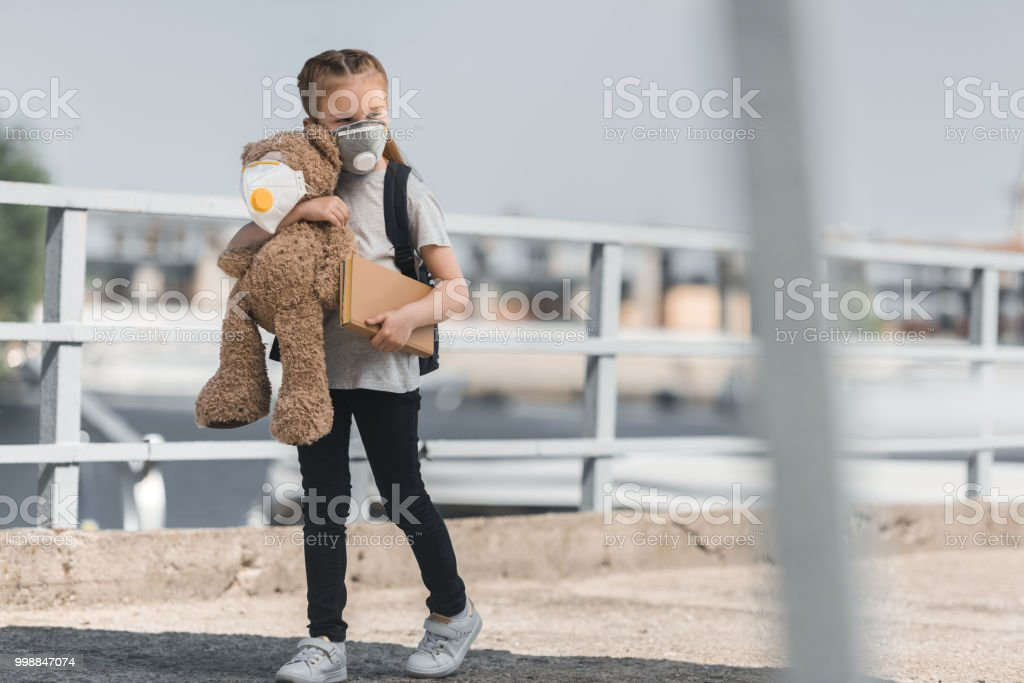kid in protective mask walking with teddy bear and book on bridge, air pollution concept stock photo