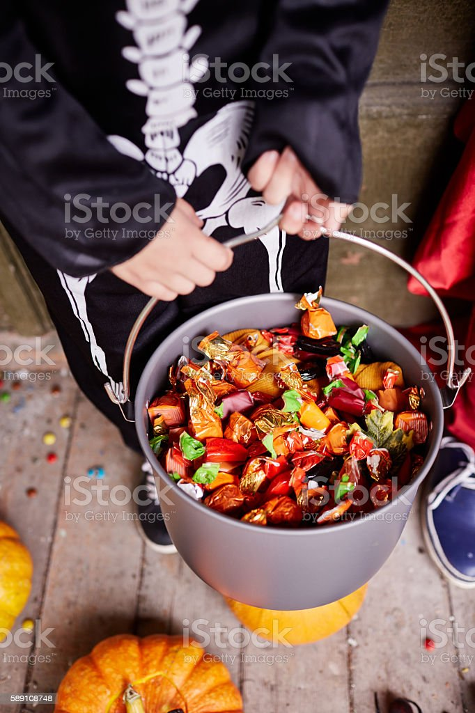Kid in skeleton costume holding a bucket full of candies stock photo