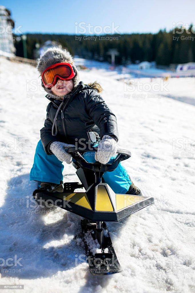 Kid in winter clothing on a snowmobile at ski resort. Lizenzfreies stock-foto