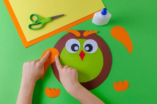 kind ist eine eule mit farbenpapier, klebstoff und schere, grün macht - diy eule stock-fotos und bilder