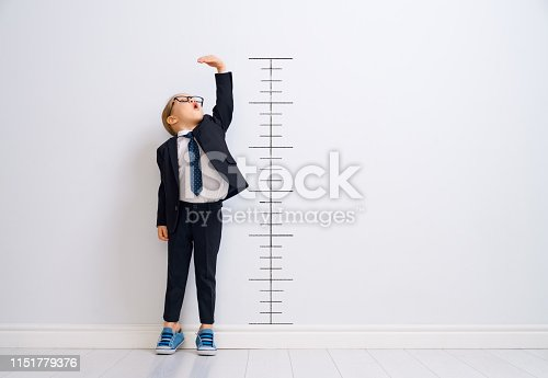 Little child is playing businessman. Kid is measuring the growth on the background of wall. Smart power concept.