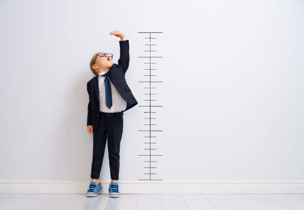 Kid is measuring the growth Little child is playing businessman. Kid is measuring the growth on the background of wall. Smart power concept. high up stock pictures, royalty-free photos & images