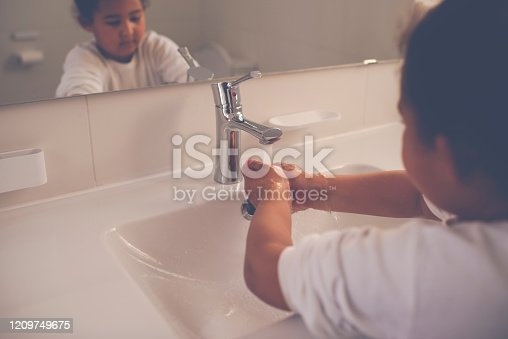 6 years, mixed-race girl washing her hands with soap in the white sink under the tap running water. Hygiene and a healthy lifestyle concept.