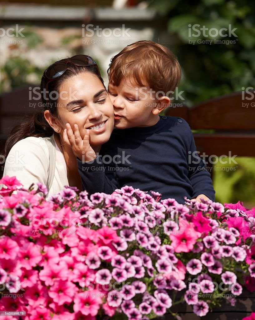 Kid kissing mother outdoor royalty-free stock photo
