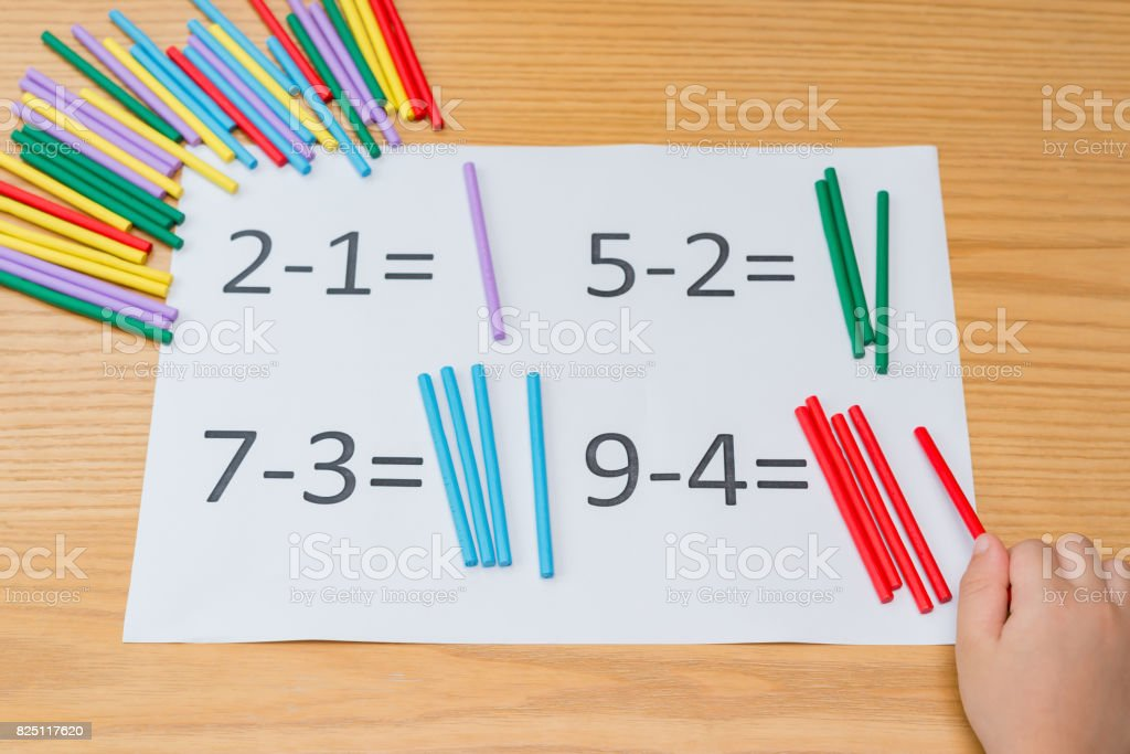 kid learning simple subtraction by counting numbers of sticks stock photo