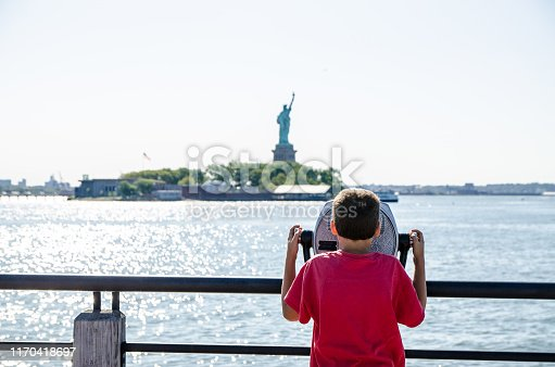Kids looking at Statue of Liberty through paying binoculars from the Liberty State Park in Jersey city during summer day