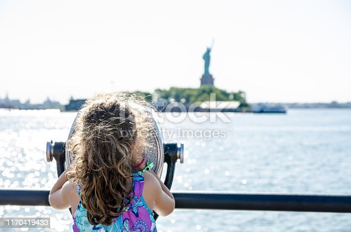 Kid looking at Statue of Liberty through paying binoculars from the Liberty State Park in Jersey city during summer day