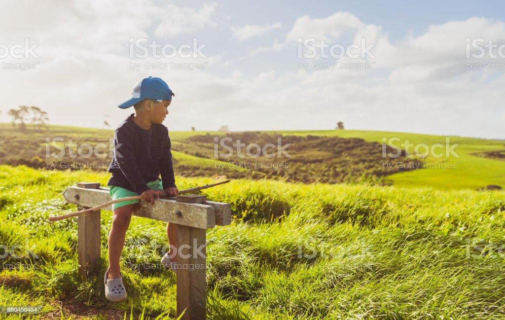 Kid looking away at coast. stock photo