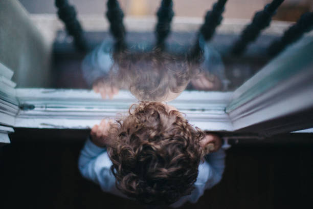 kid looking through the window - boy looking out window stock pictures, royalty-free photos & images