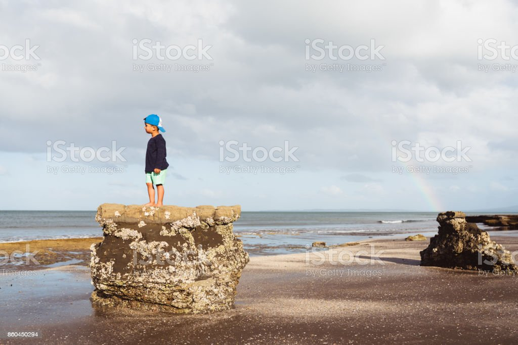 Kid looking towards coast with rainbow in background. stock photo