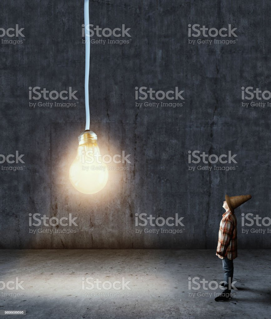 Kid looking up to a lightbulb hangs from above in a dark room. stock photo