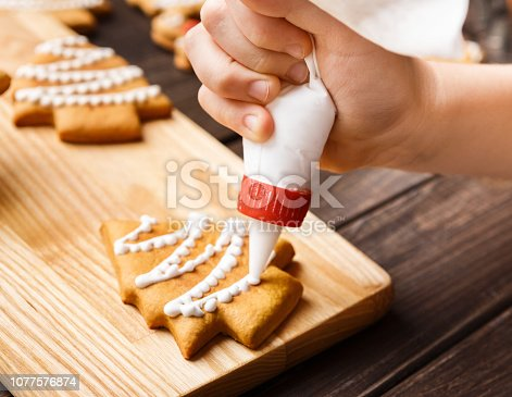 Kid making decoration on gingerbread cookie with icing, closeup