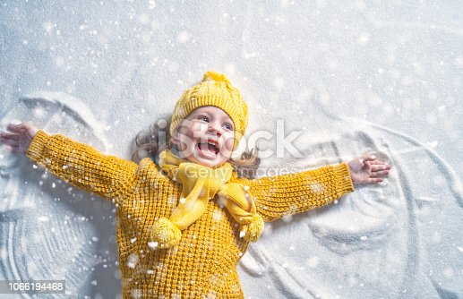 Happy child girl playing on a winter walk in nature. Kid making snow angel.