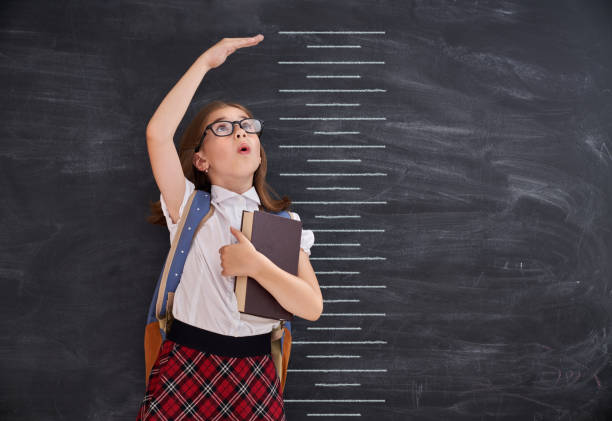 kid measures growth on background of blackboard - height measurement stock photos and pictures