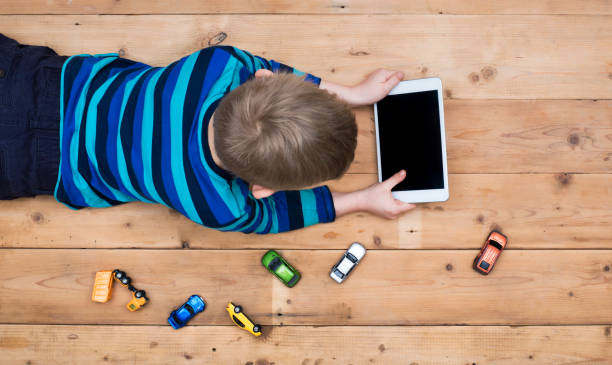 kid on floor with tablet pc stock photo