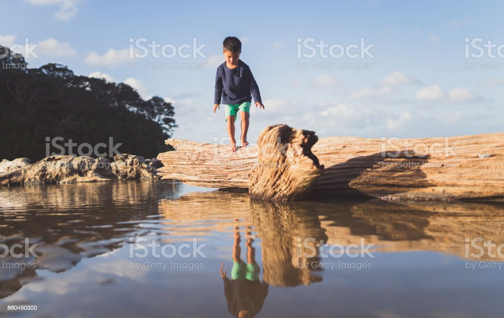 Kid on log jumping in water. stock photo