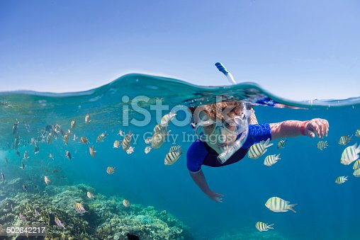 Child snorkeling over colorful tropical reef